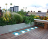 Roof terrace with decking, glass and dramatic lighting in Holland Park