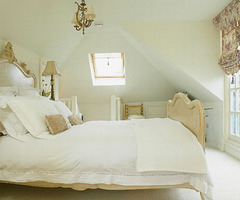 Neutral loft bedroom with antique bed and chandelier