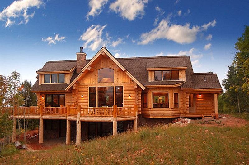 Country style handcrafted log house with dormers and sun Country log home