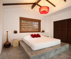 Interior Bedroom With Wooden Ceiling Beams And Polished Floors Made Of Concrete