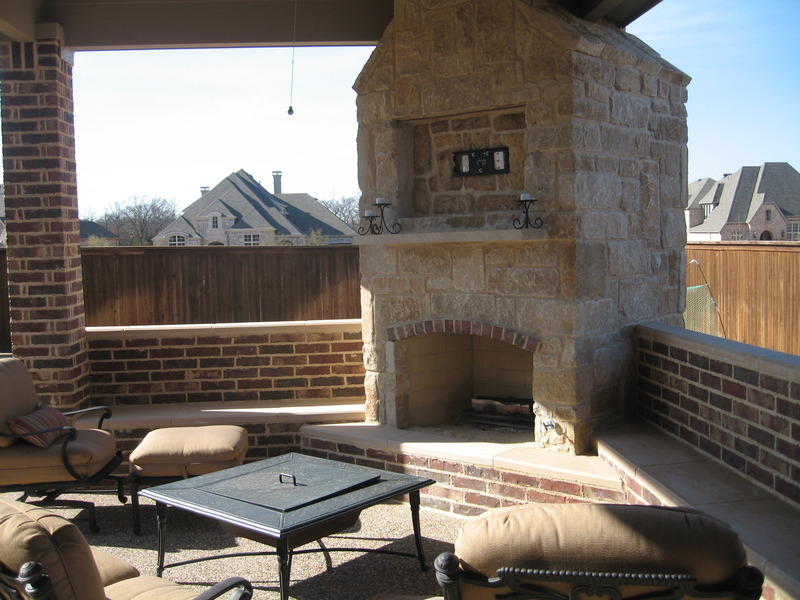 custom covered patio with outdoor kitchen and fireplace