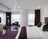 Stunning Apartment Bedroom Design With Big Bed And Long Purple Fur Rug On Wooden Laminate Flooor As Well White Bedding And Tv Setup On The Wooden Vannity Including Dark Maroon White Curtain Glass Wall