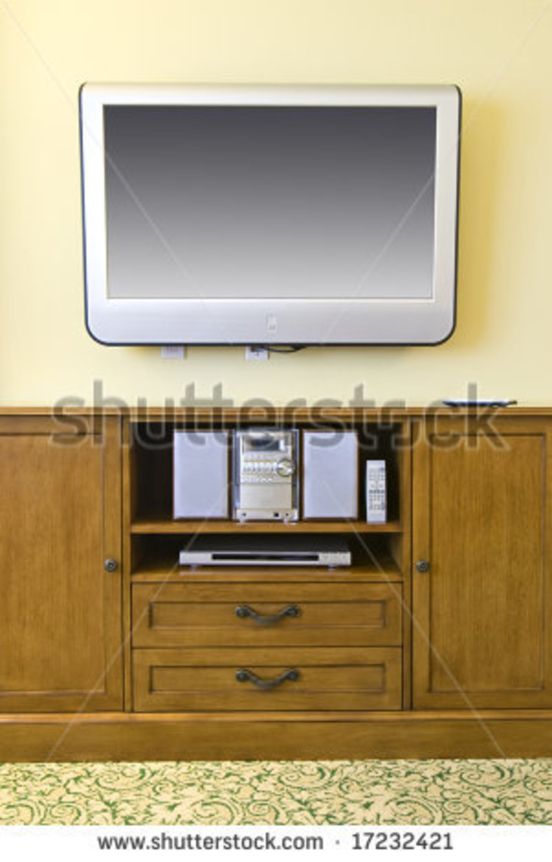 Wall Mounted Flat Screen Television Mounted Above Wooden Cabinet