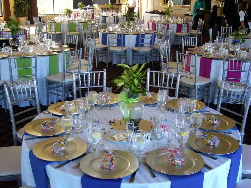 Wedding Reception Table Decorations, Possibly Neutral Tables (Beige, Tan) With Alternating Fall Colored Napkins (Green, Gold, Orange, Red)